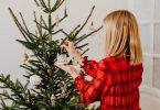 lady decorates christmas tree