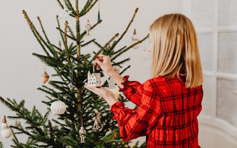 lady decorates christmas tree