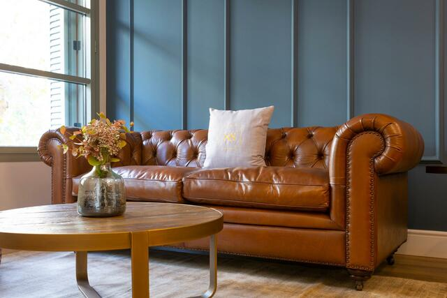 brown leather couch with blue wall