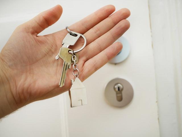hand holding keys to door