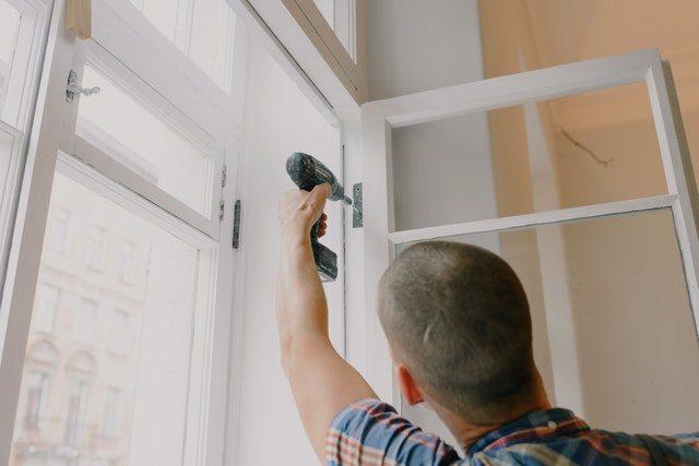 man hanging window