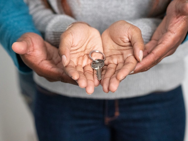 couple with hands together and key in it