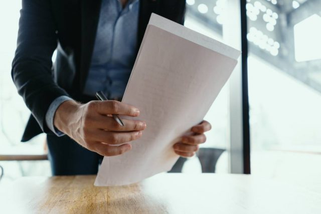 man holding papers - how to register a property in Barcelona