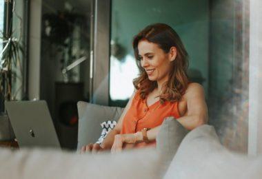 woman in orange top wokring on laptop
